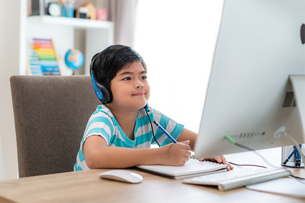 Elementary-aged student learning on desktop computer, hold pencil and notebook